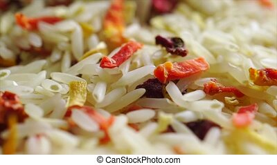 Extreme close up video of pile of uncooked rice and dried vegetables