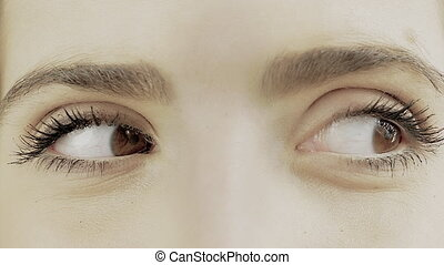 Extreme closeup of brown female eyes wondering looking left and right 4K