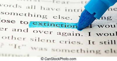 extreme closeup of extinction word on a book