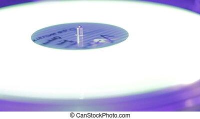 """Extreme closeup of record rotating on sound deck, light flashing"""