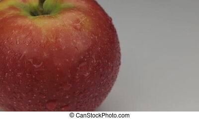 Extreme closeup red apple in drops of dew rotates on its...
