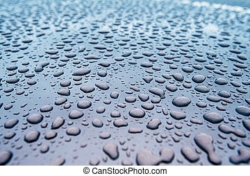 close-up of clean car paint surface with multiple water drops