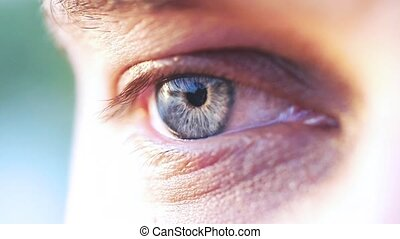 Extreme macro shot of a blue eye of young man in slow...