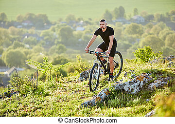 Extreme mountain cyclist riding bike on rocky trail in the countryside.