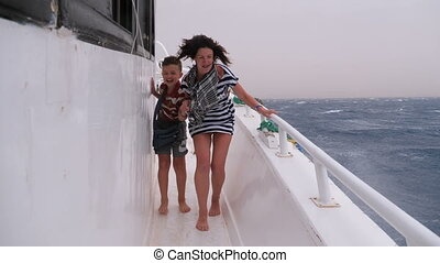Extreme Shot of Mom and Son on the Ship in a Storm. Woman...