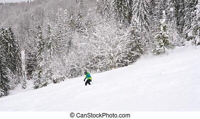 Extreme snowboarder riding fresh powder snow down the steep...