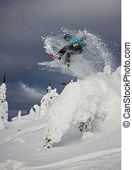 extreme snowboarder - snowboarding woman making a jump over...