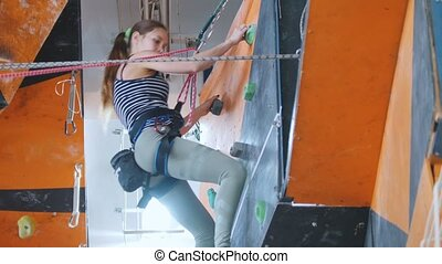 Extreme sport, bouldering. A young woman climbing up, asking...