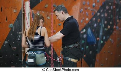 Extreme sport, bouldering. A young woman talking with her...
