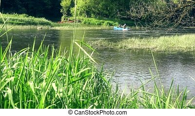 Extreme sport lovers push canoes through river water. View through reeds.