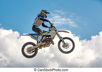 Extreme sports background - silhouette of biker jumping on motorbike on sunset, against the blue sky with clouds