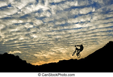 Extreme sports bike riding silhouette against stunning sunset