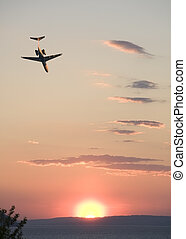 Extreme sunset flying - Low flying jet plane heading into a...