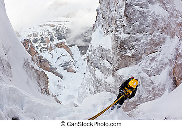Extreme winter mountaineering - Climber abseiling back down ...