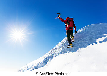 Extreme winter sports: climber at the top of a snowy peak in the Alps.