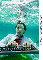 Extreme working conditions - business man working on computer typing underwater