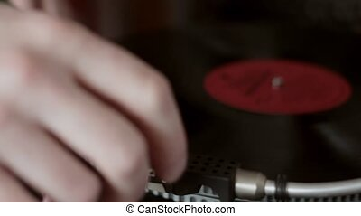 Extremely close-up male hand starting retro record player, ...