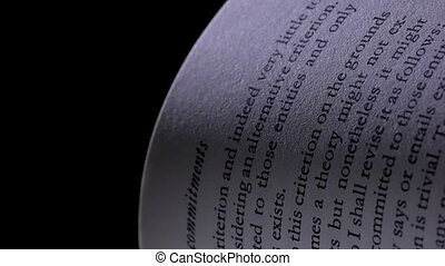 Extremely close up of an English text printed on the open pages of a book. Macro shot of turning white pages of a book in the studio on a black background. Slow motion