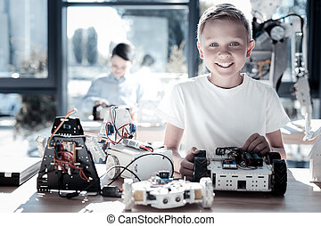 Extremely happy kid beaming while working on technological project