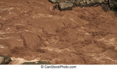 Extremely muddy, fast moving river - Close up detail of...