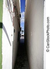 Extremely narrow street, white walls, blue sky, ...