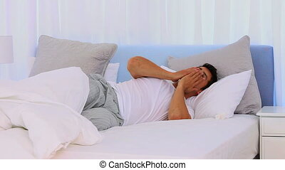 Extremly tired man sleeping fitfully in his bedroom