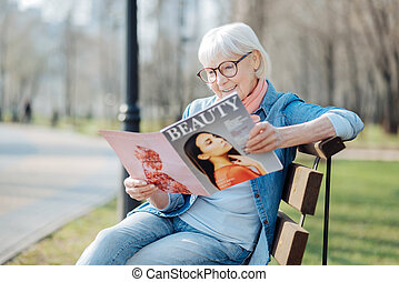 Exuberant aged woman reading a magazine