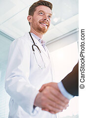 Exuberant doctor shaking hands with a businessman