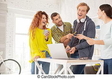 Exuberant four colleagues making fun