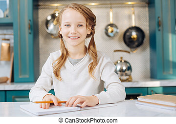Exuberant girl sitting with her notebook