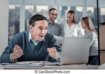 Exuberant man sitting at his laptop