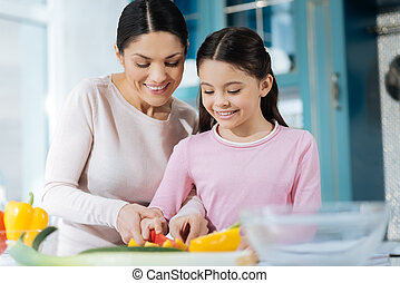Exuberant mother making a salad with her daughter