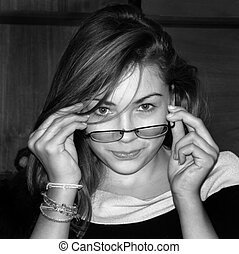 Eye Contact - Attractive young girl putting on glasses while...