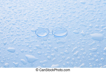 Eye contact lenses on a blue surface covered with drops of water