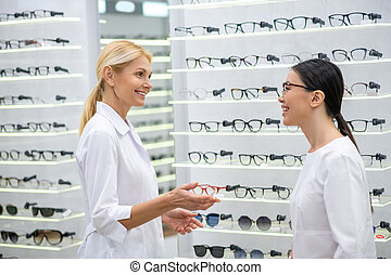 Eye doctor greeting her new assistant in the optical store