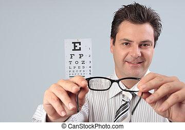 Eye doctor holds glasses
