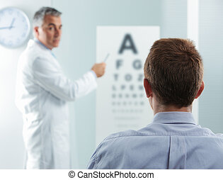 Eye exam - Optometrist and patient, doctor pointing at eye...