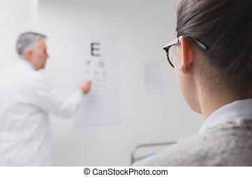 Eye exam - Woman reading the eye chart, the oculist is ...