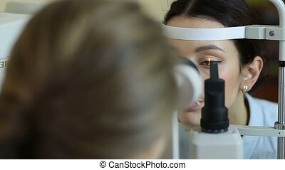 Eye examination at slit lamp in oculist office - Attentive...