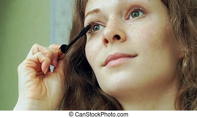 Eye in macro footage of young woman applying mascara on...