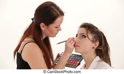 Eye make-up - Make-up artist putting on make-up on model's...