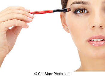 Eye make-up - Portrait of a woman applying eyeshadows