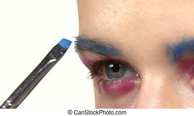 Eye make-up woman applying eyeshadow, making exotic, one, blue eyebrow, close up, on white
