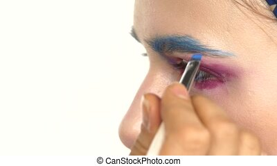 Eye make-up woman applying eyeshadow, making exotic, one, blue eyebrow, laterally, close up, on white
