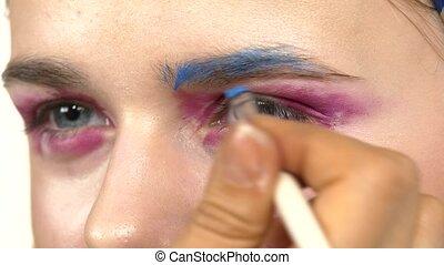 Eye make-up woman applying eyeshadow, making exotic,  two eyes, blue eyebrow, close up, on white
