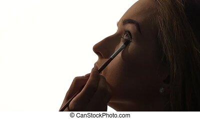 Eye makeup woman applying eyeshadow powder, Close up, silhouette. Slow motion