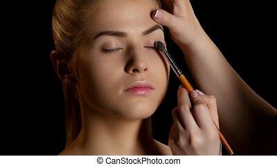Eye makeup woman applying eyeshadow powder. Makeup. Black. Closeup