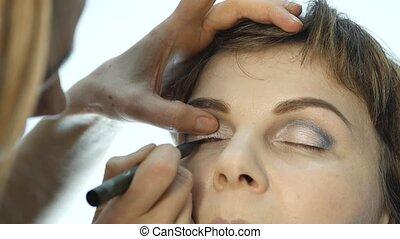 Eye makeup woman applying eyeshadow powder. Stylist is doing...
