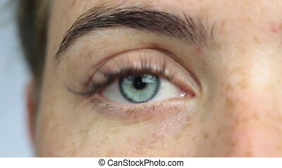 Eye of a girl with freckles close-up, woman opening her blue eye and looking around