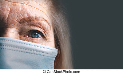 Eye of a senior woman with wrinkled skin under medical mask. Extreme close up